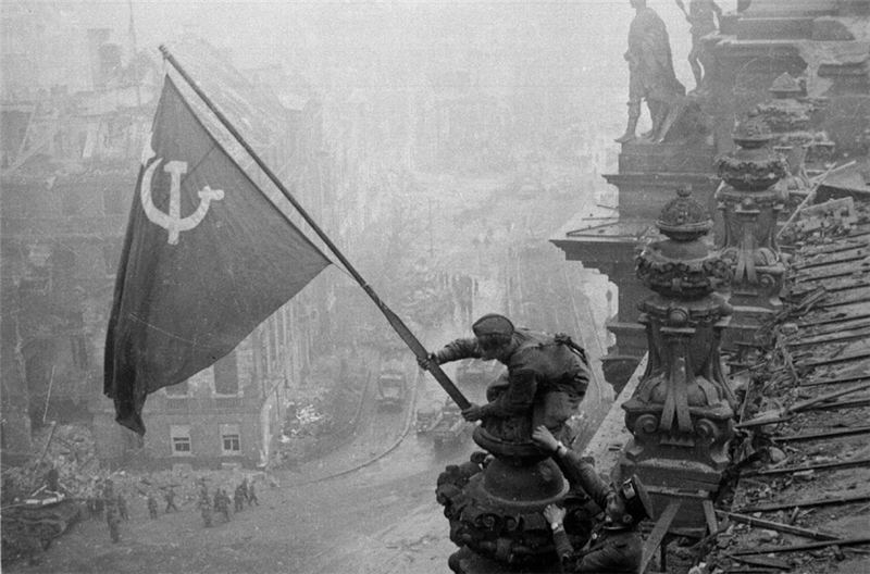 The Soviet army hoisting its flag over the German Reichstag after the battle for Berlin in 1945[