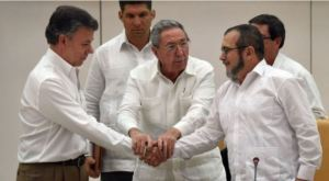 The landmark handshake between Juan Manuel Santos and Timoshenko, with two helping hands from Cuban President Raul Castro. (Justice for Colombia).