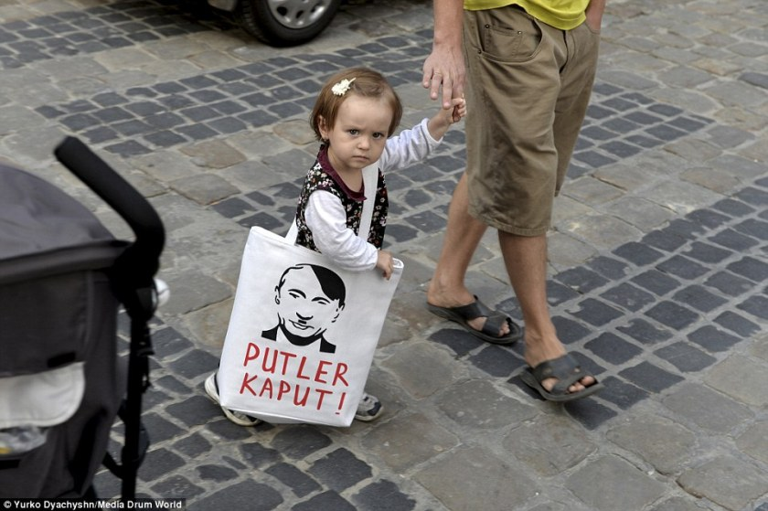 A_young_girl_carries_a_bag_with_an_image_depicting_Putin_as_the_-a-3_1417623561353.jpg